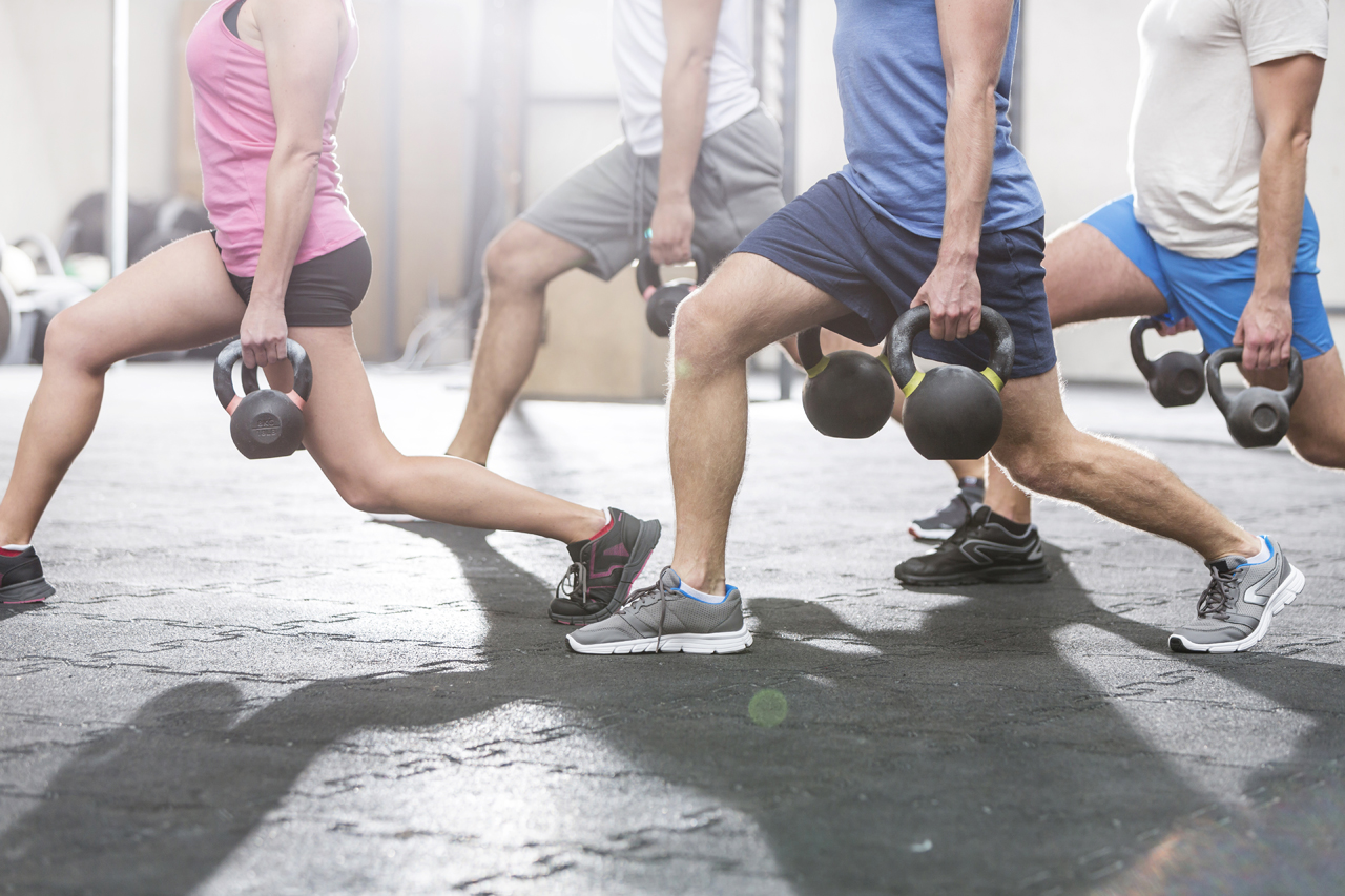 Low-section-of-people-lifting-kettlebells-at-crossfit-gym